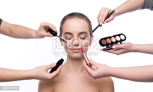 istock Hands of visagistes doing makeup for beautiful girl, isolated 953096452