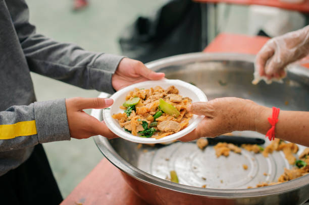 Hände von Freiwilligen dienen kostenlos Nahrung für die Armen und Bedürftigen in der Stadt : Die armen Menschen bringen einen Behälter, um Nahrung zu schöpfen, um zu essen und Hunger zu lindern und nach Hause zu bringen – Foto