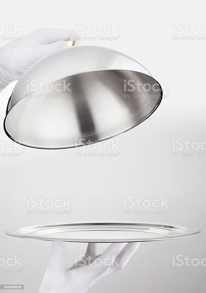 Hands of waiter opens cloche lid cover stock photo