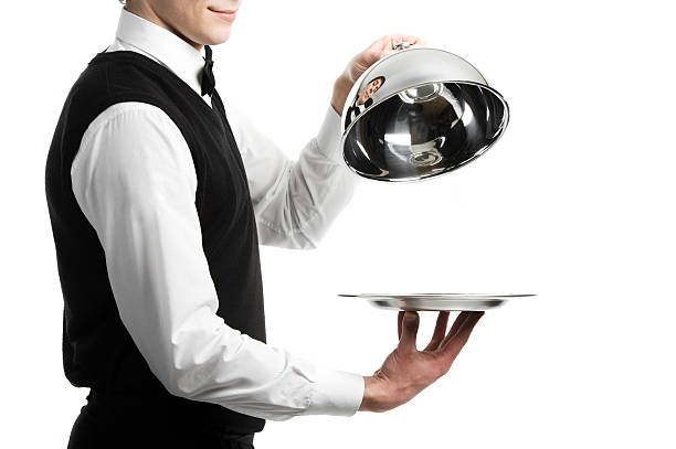 hands of waiter with cloche lid cover Close up hands of waiter with metal cloche lid cover waiter stock pictures, royalty-free photos & images
