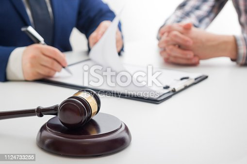 istock Hands of wife, husband signing decree of divorce, dissolution, canceling marriage, legal separation documents, filing divorce papers or premarital agreement prepared by lawyer. Wedding ring 1124733255