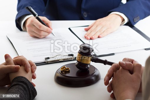 istock Hands of wife, husband signing decree of divorce, dissolution, canceling marriage, legal separation documents, filing divorce papers or premarital agreement prepared by lawyer. Wedding ring 918850974