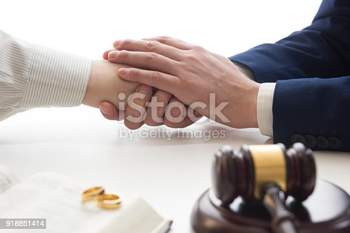 istock Hands of wife, husband signing decree of divorce, dissolution, canceling marriage, legal separation documents, filing divorce papers or premarital agreement prepared by lawyer. Wedding ring 918851414