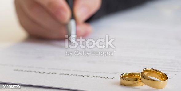 istock Hands of wife, husband signing decree of divorce, dissolution, canceling marriage, legal separation documents, filing divorce papers or premarital agreement prepared by lawyer. Wedding ring 922953720