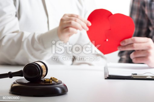istock Hands of wife, husband signing decree of divorce, dissolution, canceling marriage, legal separation documents, filing divorce papers or premarital agreement prepared by lawyer. Wedding ring 922953930