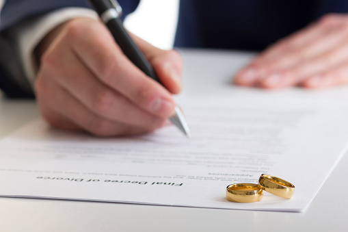 istock Hands of wife, husband signing decree of divorce, dissolution, canceling marriage, legal separation documents, filing divorce papers or premarital agreement prepared by lawyer. Wedding ring 923438432