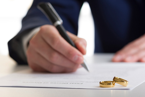 istock Hands of wife, husband signing decree of divorce, dissolution, canceling marriage, legal separation documents, filing divorce papers or premarital agreement prepared by lawyer. Wedding ring 924467588