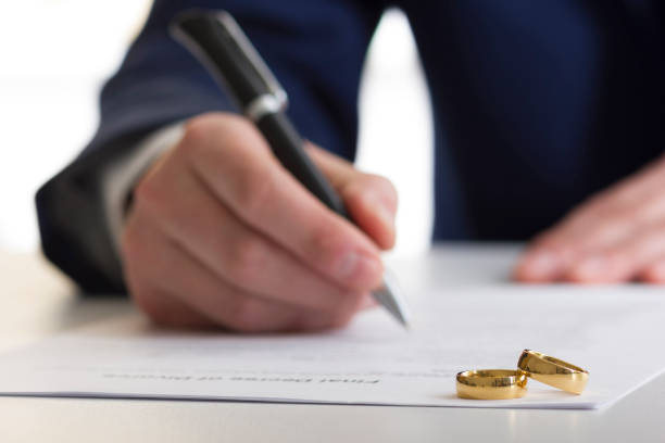 hands of wife, husband signing decree of divorce, dissolution, canceling marriage, legal separation documents, filing divorce papers or premarital agreement prepared by lawyer. wedding ring - divorzio foto e immagini stock