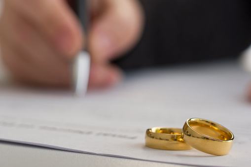istock Hands of wife, husband signing decree of divorce, dissolution, canceling marriage, legal separation documents, filing divorce papers or premarital agreement prepared by lawyer. Wedding ring 926241578