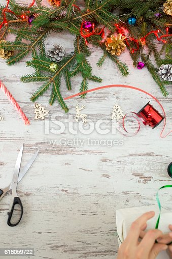 istock Hands of woman decorating Christmas gift box 618059722