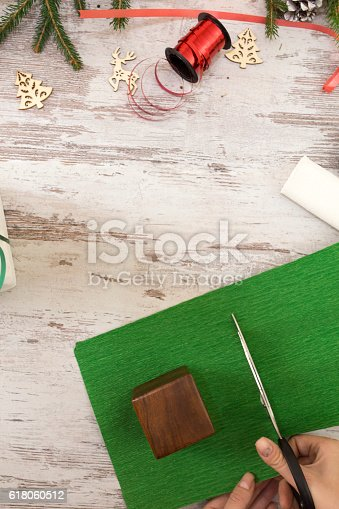 istock Hands of woman decorating Christmas gift box 618060512
