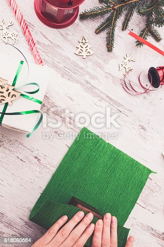 istock Hands of woman decorating Christmas gift box 618060584