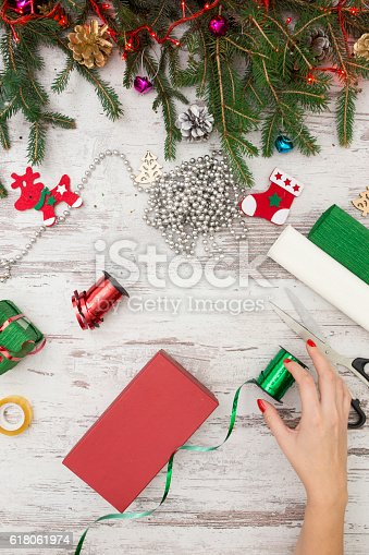 istock Hands of woman decorating Christmas gift box 618061974