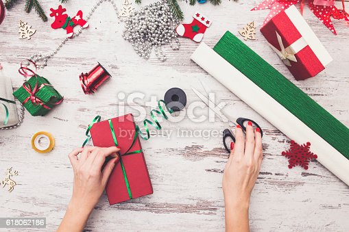 istock Hands of woman decorating Christmas gift box 618062186