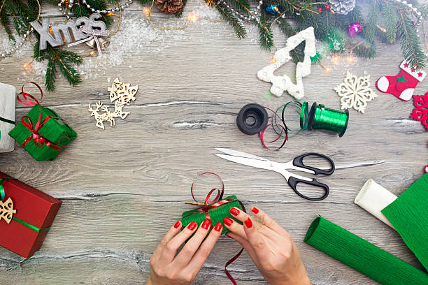 hands of woman decorating christmas gift box - bastelkarton stock-fotos und bilder