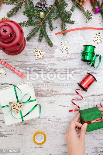 istock Hands of woman decorating Christmas gift box 624102692