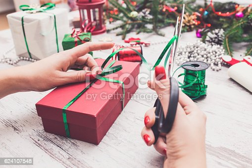 istock Hands of woman decorating Christmas gift box 624107548