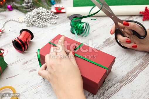 istock Hands of woman decorating Christmas gift box 624107622
