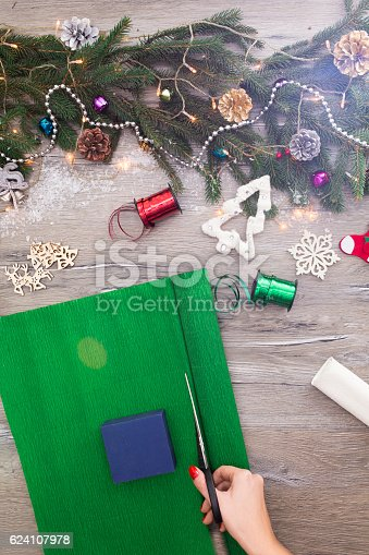 istock Hands of woman decorating Christmas gift box 624107978