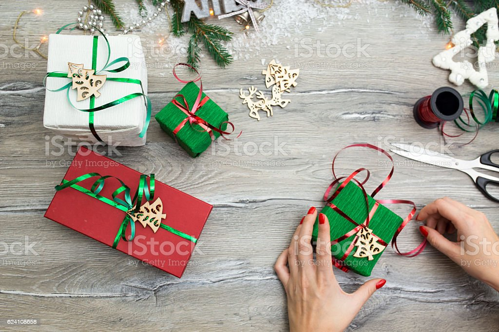 Hands of woman decorating Christmas gift box stock photo