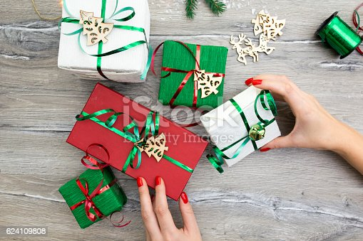 istock Hands of woman decorating Christmas gift box 624109808