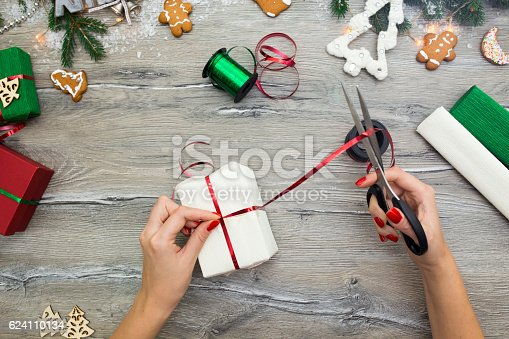 istock Hands of woman decorating Christmas gift box 624110134