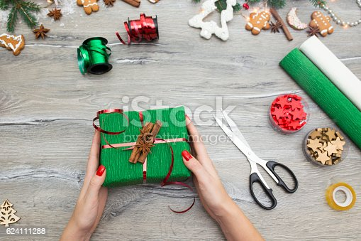 istock Hands of woman decorating Christmas gift box 624111288
