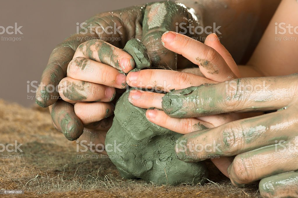 hands of woman helping child to work with raw clay stock photo