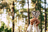 hands of woman holding a wooden heart with at the background a wood or forest - save the forest and change climate concept lifestyle