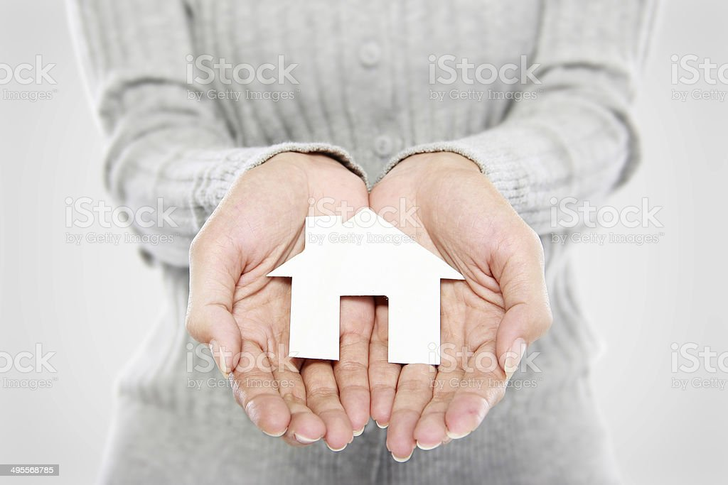 Hands of woman holding paper house stock photo