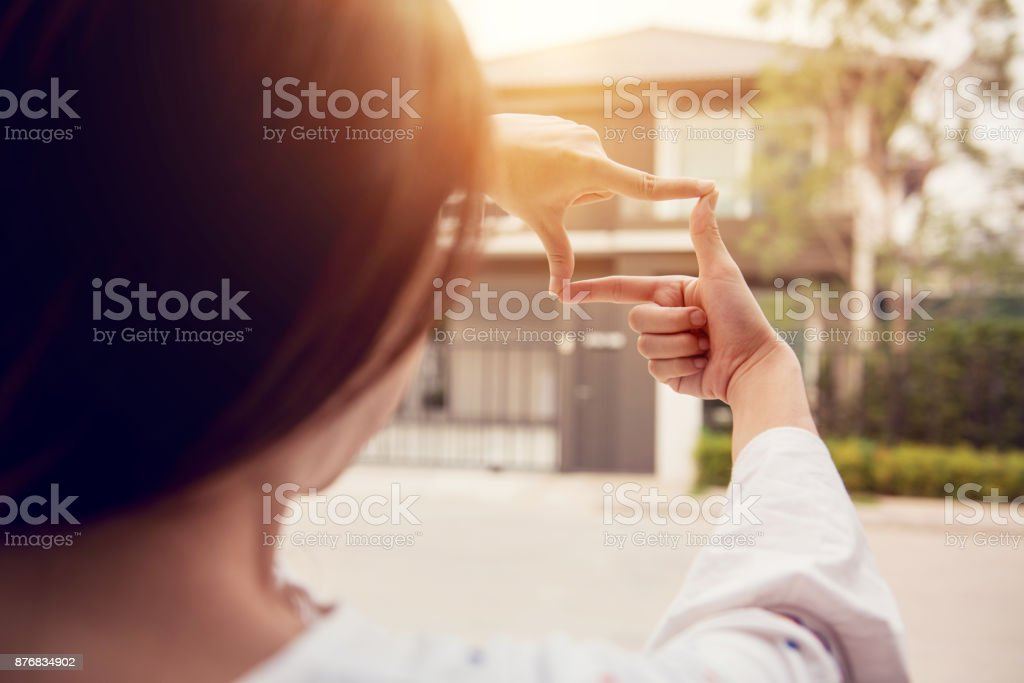 Hands of woman making frame gesture with home background. Planning for the future resident concept. Hands of woman making frame gesture with home background. Planning for the future resident concept. Adult Stock Photo