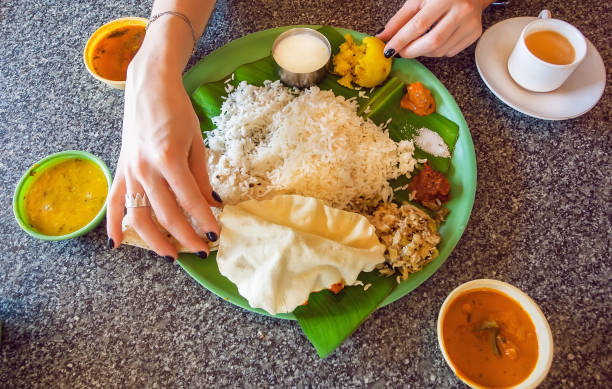 hands of woman on table with traditional south indian food thali with rice and spicy vegetables on palm leaf. - dieta macrobiotica foto e immagini stock