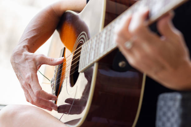 Hands of woman playing acoustic guitar stock photo