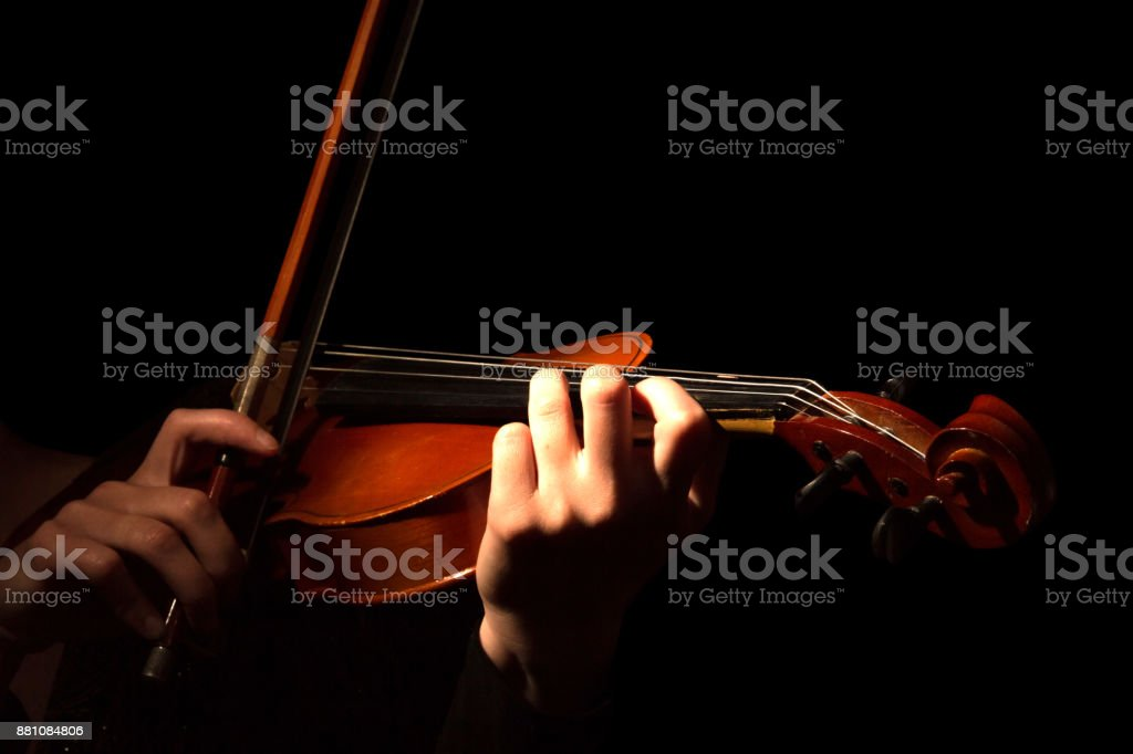 Hands of woman playing violin isolated on black stock photo
