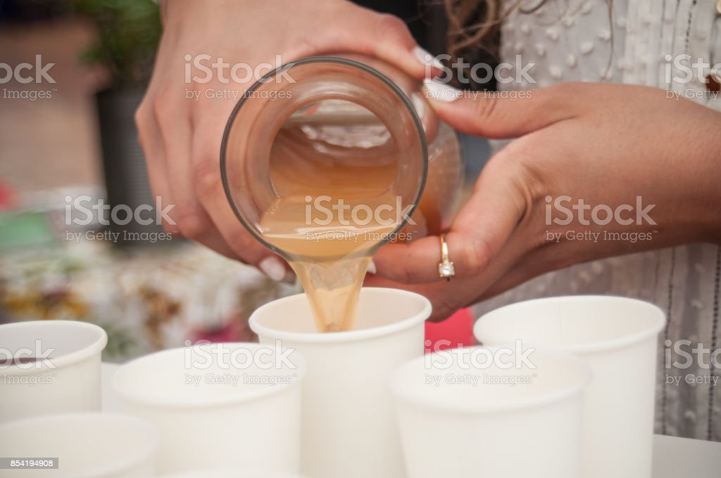 hands of woman pouring apple juice in plastic cups stock photo