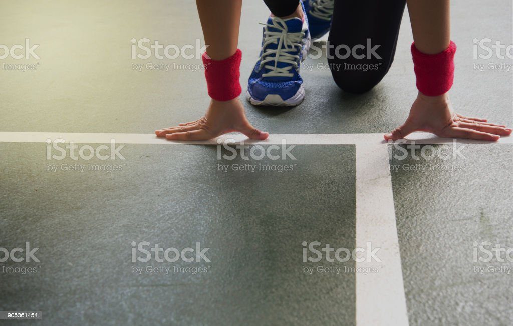 hands of woman runner with blue sport shoes at start line on gymnasium floor background stock photo