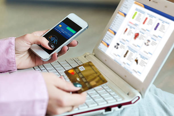 Hands of Woman shopping on-line holding credit Card and Telephone stock photo