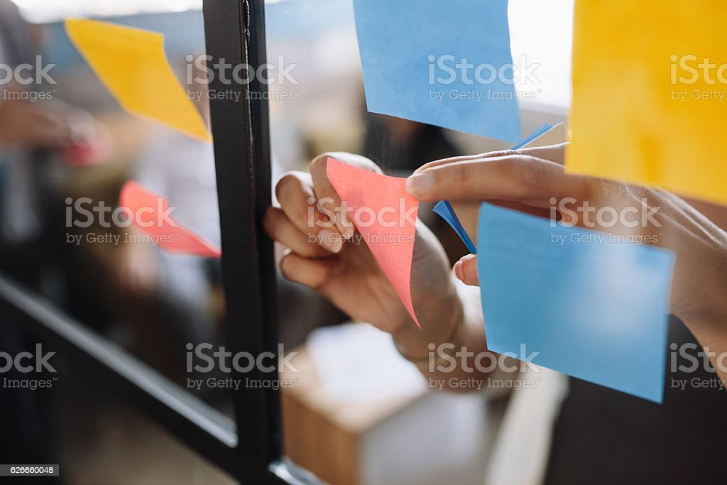 Hands of woman sticking adhesive notes on glass stock photo