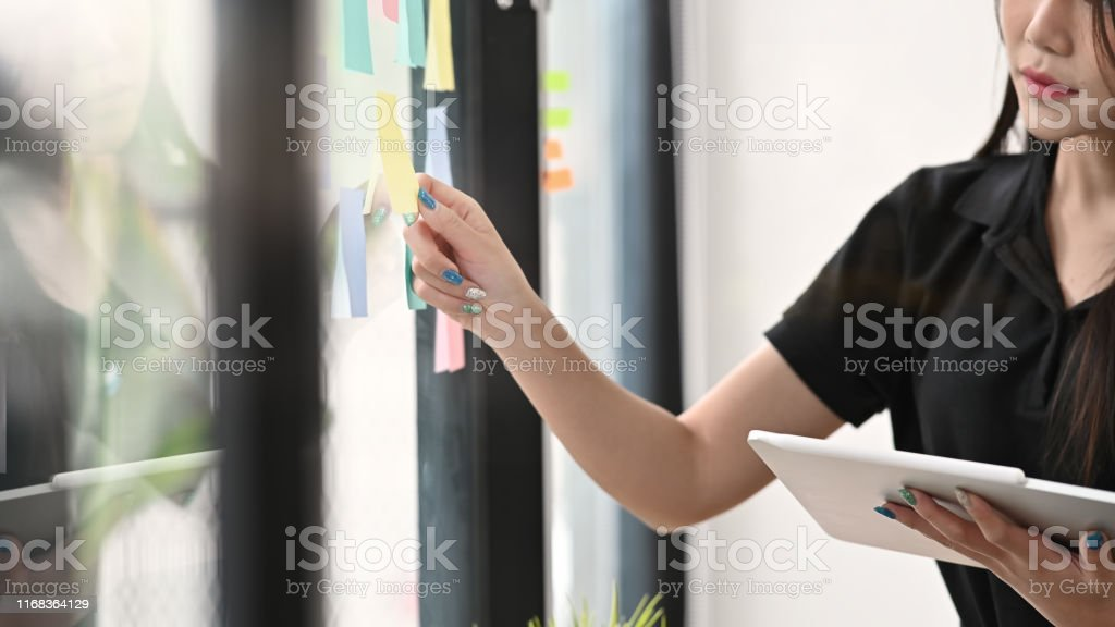 Hands of woman sticking adhesive notes on glass windows in office.
