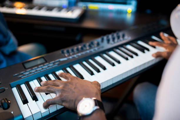 Hands of young African composers or musician touching keys of pianoboard Hands of young African composers or musician touching keys of pianoboard while working in sound recording studio keyboard player stock pictures, royalty-free photos & images