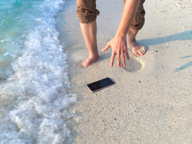 hands of young asian man dropping mobile smart phone on tropical sandy beach. accident and insurance electronic equipment concept - broken iphone stock photos and pictures