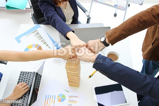 Hands of young business people giving fist bump together to greeting complete dealing in office. Success and teamwork concept.