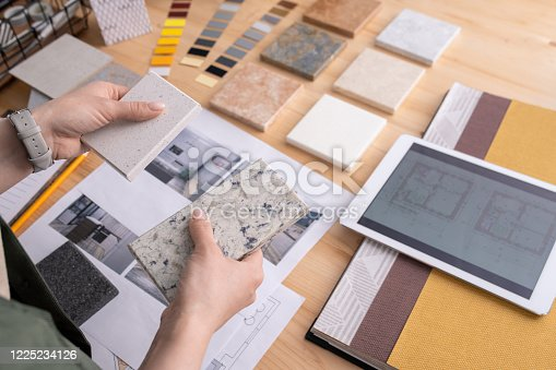 512113530 istock photo Hands of young female designer holding two samples of marble tile over table 1225234126