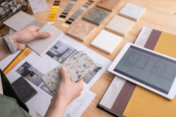 Hands of young female designer holding two samples of marble tile over table stock photo