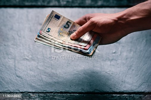Hand´s of young man holding a money. Banknotes on a stone background. Euro money bank notes of different value. European currency - Euro. Bills of money. Man holding a bills of money.
