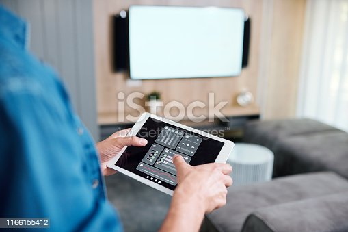 Hands of young man holding tablet with smart remote control system while adjusting volume or choosing channel