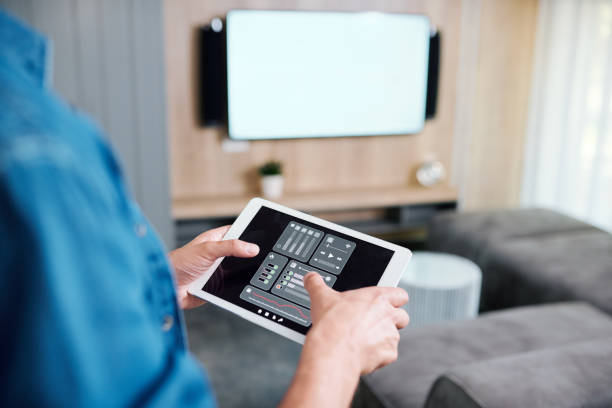 Hands of young man holding tablet with smart remote control system stock photo