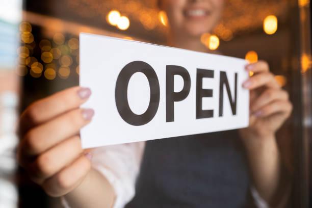 Manos de joven propietario de restaurante o cafetería poniendo aviso abierto en la puerta - foto de stock