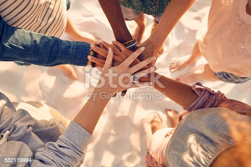 Closeup image of hands of young people with on stack. Group of mixed race friends on the beach with their hands stacked.