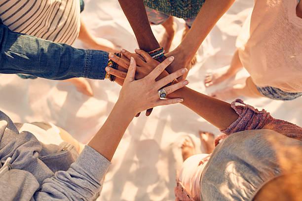 Manos de gente joven en pila en la playa - foto de stock